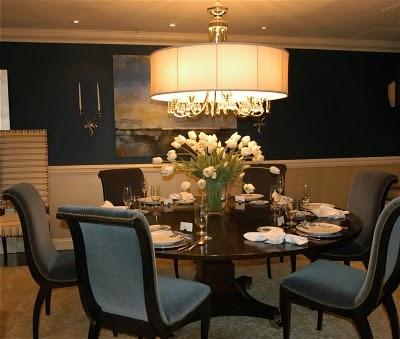 Navy blue dinning room with beautiful light fixture.
