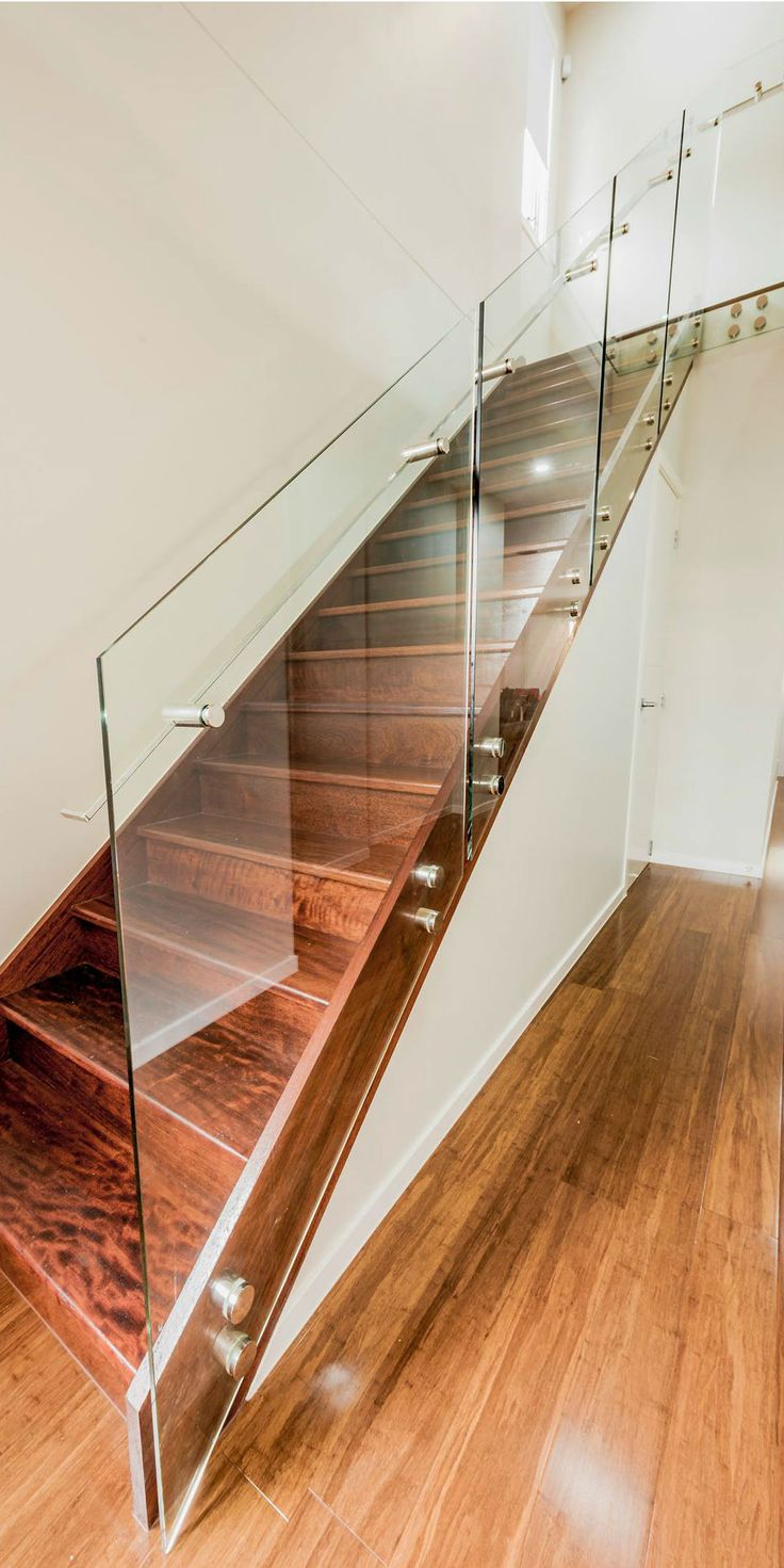 Glass staircase with stainless steel custom made handrails by Miami Stainless.