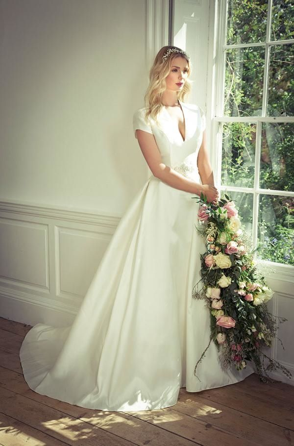 A bride wears an elegant wedding dress with tailored bodice, deep v neckline and cap sleeves