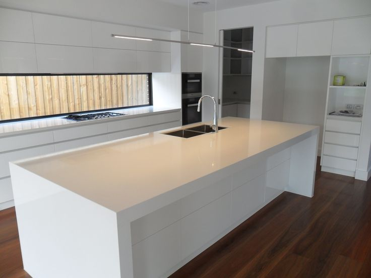 Contemporary kitchen in white. Fixed window as a splash-back, sink & dishwasher in the island bench. Client's own lighting imported from Netherlands.