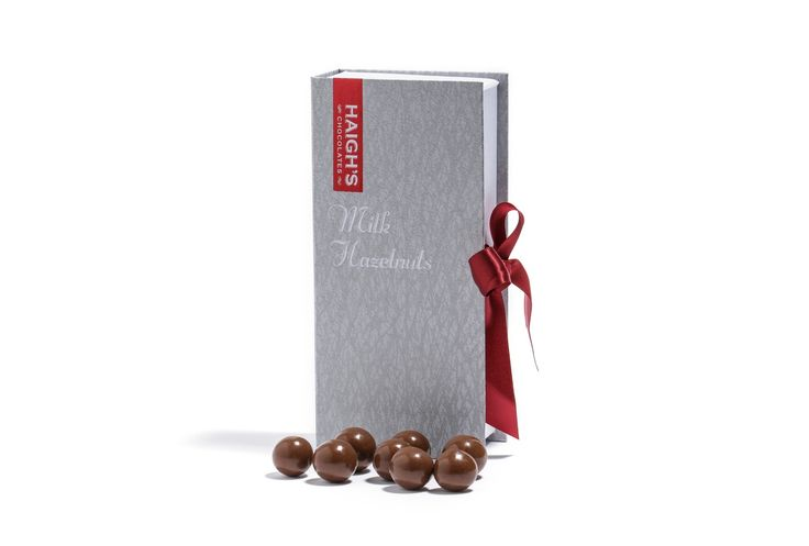 Haigh's Chocolates –Milk Roasted Hazelnuts Whole roasted hazelnuts, pan coated in layers of premium milk chocolate in a ribboned silver book box. #HaighsOnline #Christmas #Chocolate #Gifts