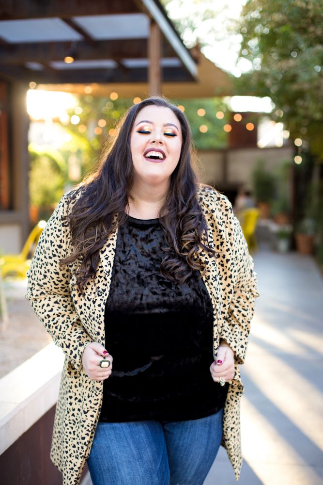 Plus Size Women's black crushed velvet t-shirt, vintage animal print jacket, ripped jeans, and a few statement rings.