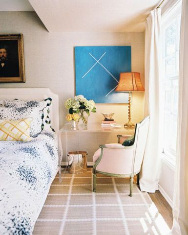 Create a warm and inviting workspace in your bedroom with a transparent waterfall table and a French-style chair beside an upholstered bed. Add decorative florals for a colorful touch.