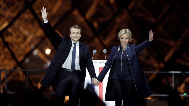 """Francie si nezvolila """"Trumpa"""", tedy Marine Le Penovou, ale centristu Emmanuela Macrona. Na snímku slaví s manželkou Brigitte vítězství na pódiu v Paříži."""