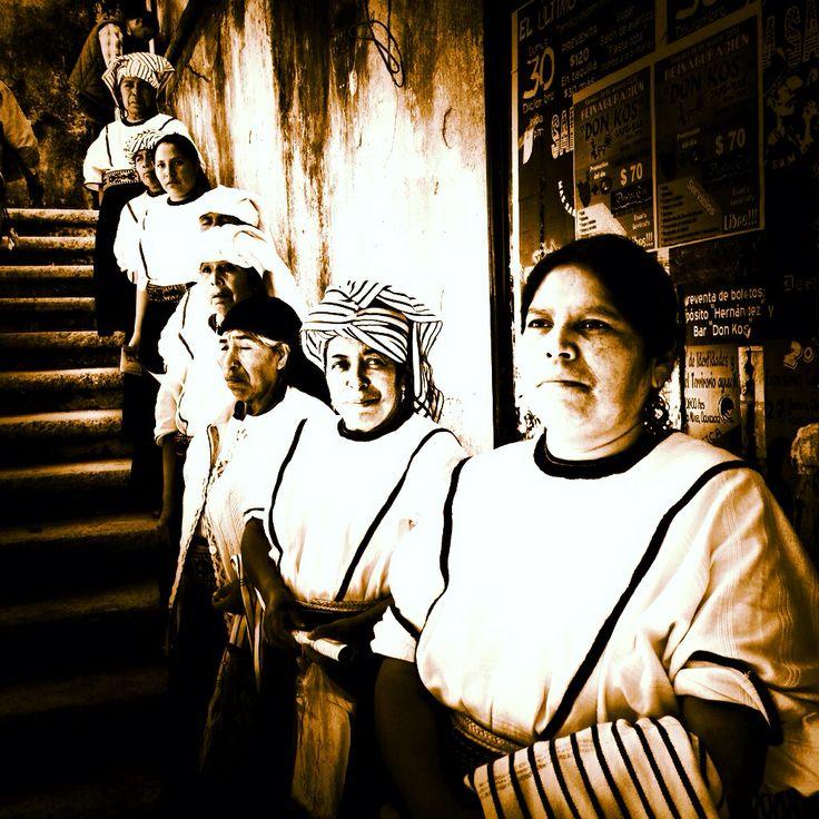 Mujeres Mixes de #Oaxaca, en #Tamazulapan que todavía visten huipiles.   Son blancos sin dibujos, de tres lienzos unidos por una randa roja.  El escote cortado en redondo, tiene como adorno una cinta.  El enredo, de dos lienzos cosidos a lo largo es también de tela de fábrica, de algodón azul marino, y tableada con pliegues todo alrededor. Lo sostiene un ceñidor tubular de palma trenzada cubierto por una faja de algodón con dibujos de figura humana y de grecas en dos colores.