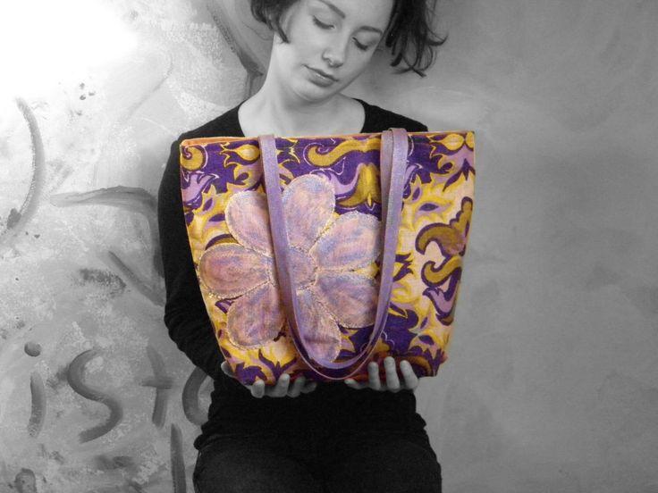 Originál kabelka - lila květina Originální kabelka zdobená našitou aplikací ve tvaru květiny. Květina i držadla jsou patinované textilními barvami. Kabelka je ušitá z dnes již nesehnatelné látky, vyrobené v československé textilce. Jen jeden originální kus - nelze vyrobit stejný, pouze podobný. Vyztuženo. Vypodšívkováno. Magnetické zapínání. Rozměry: 40x30x13cm