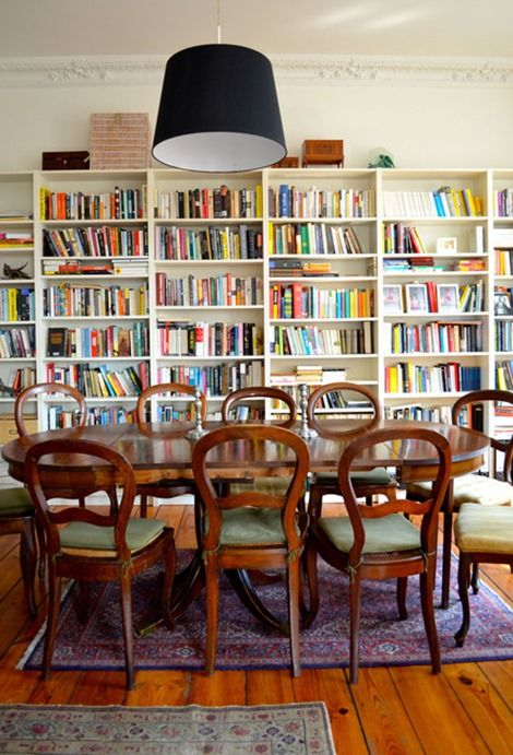 bookshelves in dining room apt therapy. Love the full bookshelves! Also like the back drum light with brown chair.s