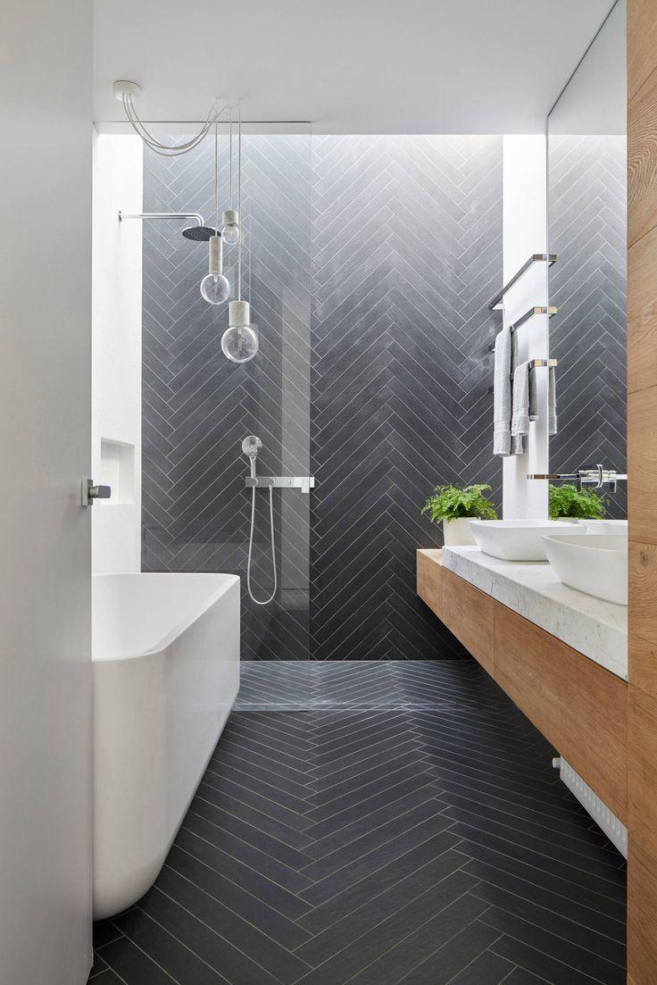 Adoramos a textura em chevron criada pelo escritório MMAD Architecture para a parede deste banheiro! A combinação dos ladrilhos acizentados com a marcenaria e o mármore deu um ar sofisticado para o projeto.