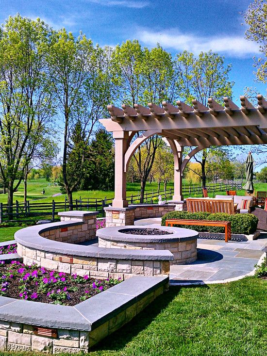 Stone terrace built to take advantage of the territorial golf course view: pergola covered patio and firepit encircled by tiered walls for seating and planters.