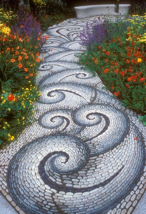 Stone walkway in the garden leading to a garden bench, with twists and twirls in pattern, along vibrant flower garden of red, yellow, orange, and purple, inlcuding Geum, Achillea, Salvia perennial...