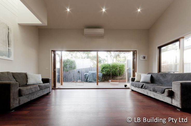 Lounge design inspiration. Indoor/ outdoor living. Smoked baltic bi-fold doors with cedar posts and kids rustic wooden swings to keep them entertained. www.lbbuilding.com.au