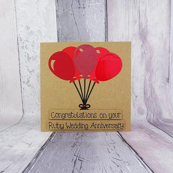 40th anniversary card. This ruby wedding anniversary card for a couple features a large bunch of balloons in shades of red with a red accent gem. This would make a great card for a couple celebrating their anniversary or for your significant other.  This handmade anniversary card has a lots of balloons held together by black strings into a bunch. The balloons are a mixture of different shades of red and different textures of card including metallic and glossy card. The sentiment on this…