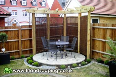 New round patio with pergola and mini hedge shows the