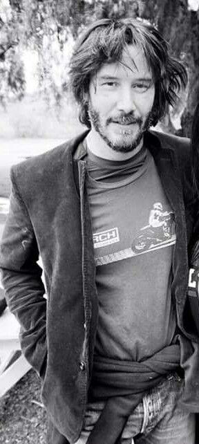 Scruffy off-duty Keanu. I'm so into the jumper tidied around his waist