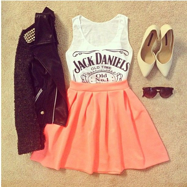 Studded black jacket over a white tank top tucked into a coral skater skirt, white heels, and glasses