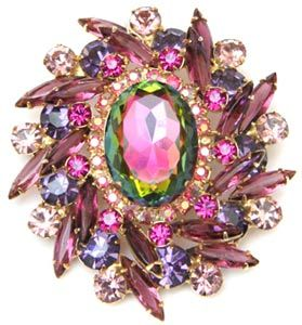 A green watermelon stone anchors the heart of this circa-1960 Juliana brooch, which also features fuchsia rhinestones and aurora borealis highlights.