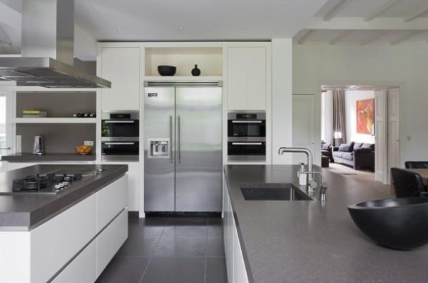 Witte greeploze keuken met grijs werkblad.
