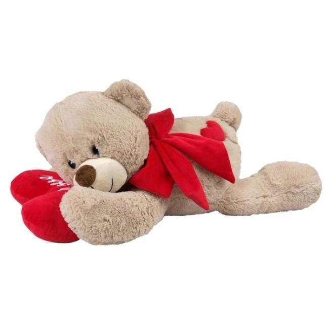 """Leuke teddybeer voor als Valentijnsdag cadeau. Gemaakt van extra zacht pluche, licht beige in kleur met een rode strik,en rood hartvormige kussen met hierop de tekst """"Love""""."""