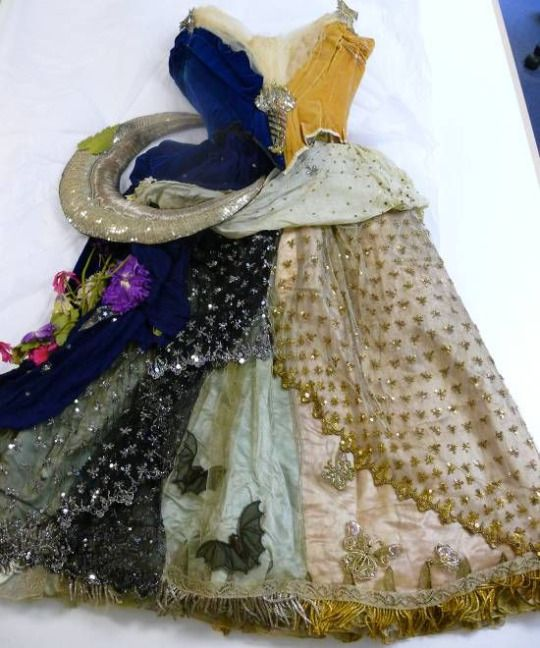 NIGHT&DAY dress by C.F. Worth 1858 - A fancy dress costume made of blue and yellow silk. The silk velvet bodice is boned and lined with cream silk. The multilayered skirt has decorative elements such as butterflies, bats, flowers, a stuffed bird and a padded silver moon crescent, all attached onto the skirt and further trimmed with beads and sequins. This fancy dress costume includes the original silk slippers, one for Night, one for Day, and a feather fan, also split into ni