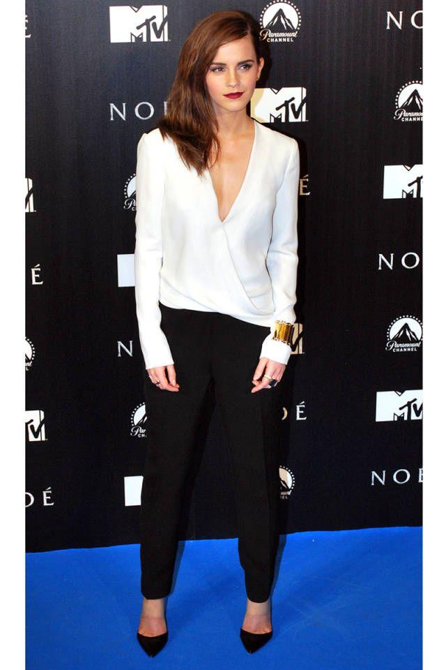 Emma Watson con un look clásico de camisa blanca y pantalones negros, perfecto para la noche.