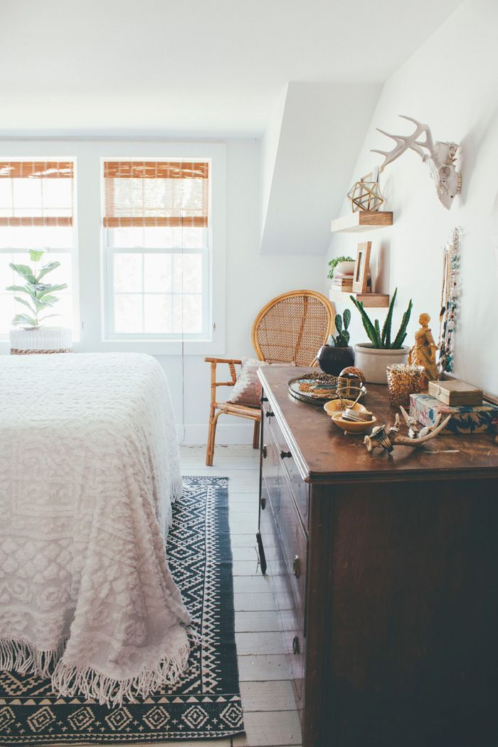 apartment bedroom, boho bedroom, wicker chair, blue rug, antlers