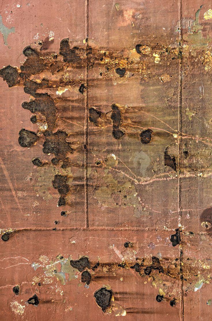 Deel van een roodbruine scheepsromp met lasnaden, roestvlekken en afbladderende verf. - Part of a ship hull with welds, rust and peeling paint.