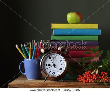 Стопка книг в разноцветных обложках, карандаши, будильник и ветка рябины на столе. Натюрморт. Обратно в школу. 1 сентября. День учителя.