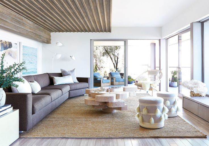 This eclectic living room's neutral and beachy hues, relaxed sectional sofa, and big, bright windows create the perfect beach house look.