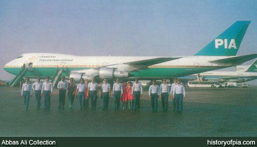 Crew of Pakistan International Airlines (PIA) Boeing 747-200B (AP-AYW) photographed at Karachi Airport in 1980s. Saudia Lockheed L-1011 TriStar also visible in the background.