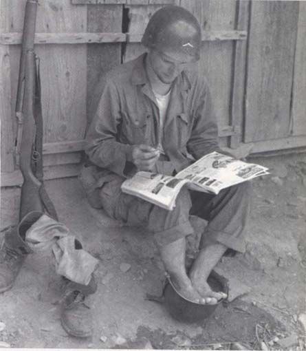 Solider demonstrates the versatility of the standard U.S. Army helmet to soothe his feet during the Korean War. (U.S. Army/History By Zim)