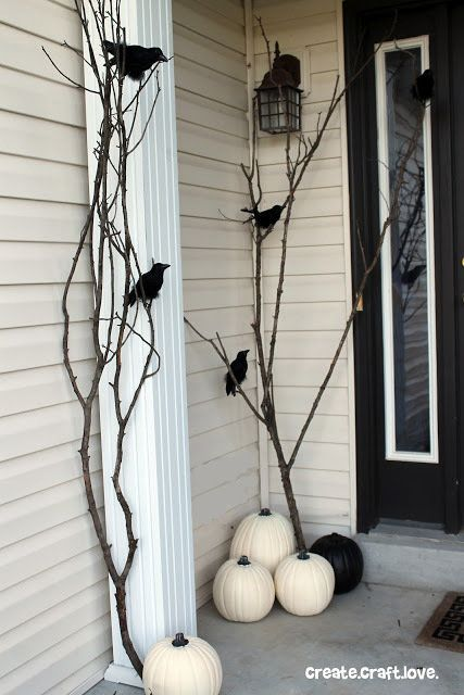 Foraged fallen branches, white pumpkins, and fake birds lend a rustic look with a hint of spookiness to this <a