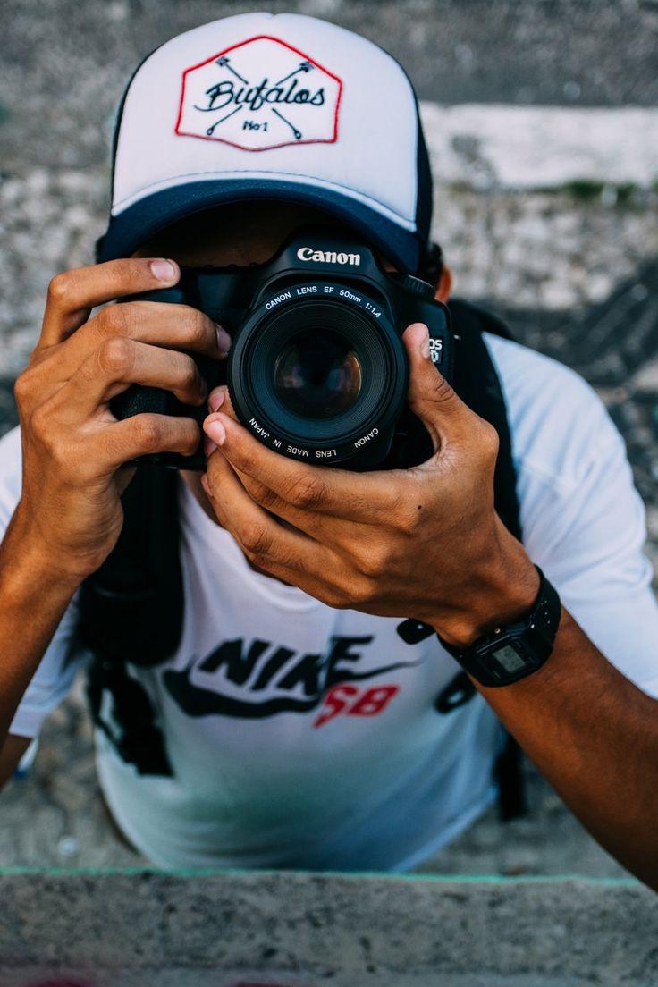 Man Wearing White Nike Sb Shirt Holding Black Dslr Camera