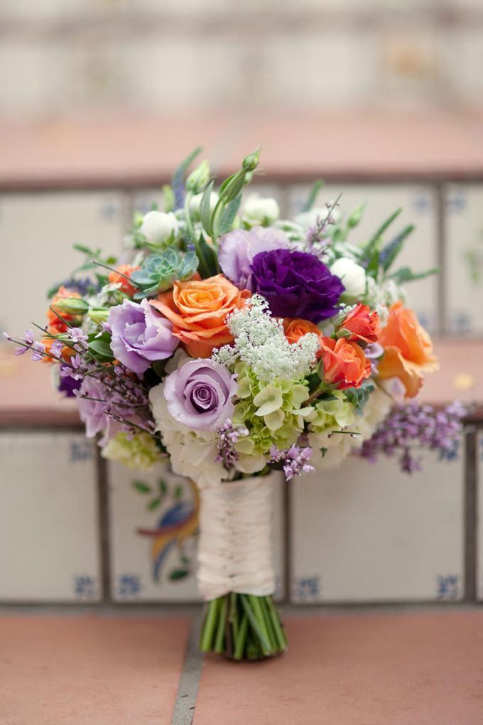 Orange, lavender, purple, and green bridal bouquet. Purple, lavender, and green are excellent complimentary colors with orange and peach.