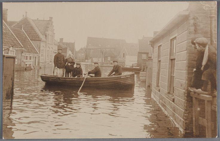 Volendam, Watersnood 1916 Straatbeeld van Volendam tijdens de watersnood. Op de voorgrond een roeiboot van de politie. Jongens op een hek. #NoordHolland #Volendam