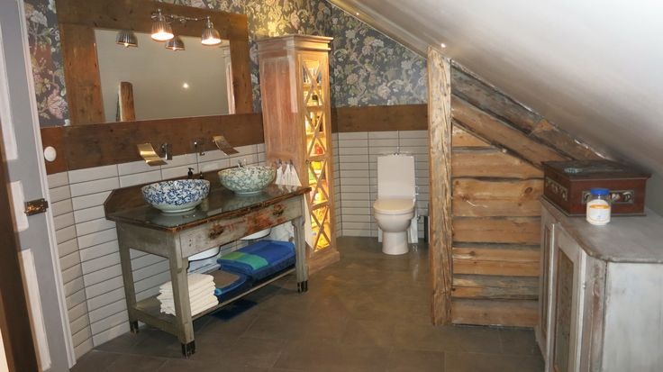 Toilette in old fashion style with ceramic bowls for the water. Old wooden plank mounted on the wall
