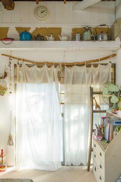 海で拾ってきた木を使ってカーテンレールに。コットンの布で作ったカーテンをかける。