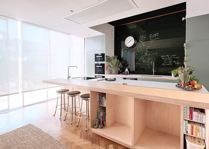 Open shelving under the spacious island in professional chef, Anna Hansen's kitchen provides additional storage for recipe books