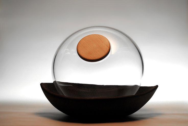 Urna funeraria de vidrio apoyada sobre una bandeja de cerámica negra. Para cenizas y flores o pequeños objetos para el difunto.
