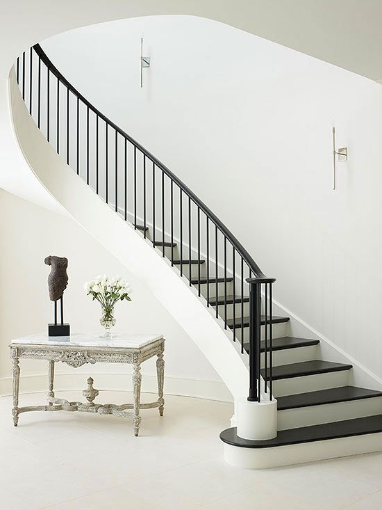 Flowing Staircase - Flowing down like the train of an elegant gown, this staircase creates a dramatic style statement. The dark wood treads and metal balustrade lend contrast to the otherwise all-white foyer.