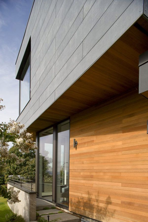 cement board - cedar - black windows.  This illustrates our love of the mix of two cladding materials rather than using render. but have no idea on costs of cement board over render?
