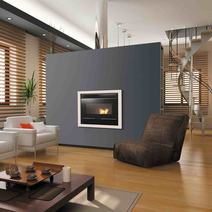 insert cheminée par Godin encastrée dans un mur repeint en gris anthracite, fauteuil en velours marron foncé et sol en parquet massif