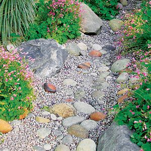 Build a dry creek bed with boulders, cobblestones, and pebbles. I like the look. It could break up our yard that is heavy with bark dust. Posted on Sunset.