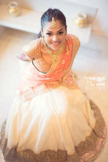 A young bride in an ivory and peach Sabyasachi lehenga at her wedding in Udaipur. Photographed by wedding photographers - The Wedding Nama
