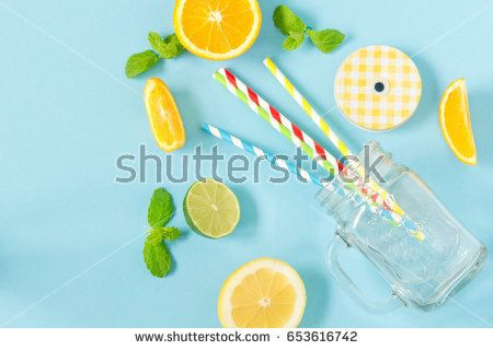 Empty mason jar with colorful paper straws and sliced fruits on blue background, top view. Preparation for summer drinks like cocktail, lemonade, juice.