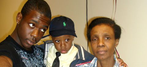 Ramarley Graham, wearing a black T-shirt, holds his little brother wearing a bow tie, his brother Chinnor Campbell, behind their grandmother Patricia Hartley, who is wearing a plaid shirt
