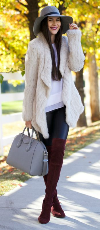 Rachel Parcell wears red over the knee boots with a stylish cream fur coat and leather leggings.   Coat: June, Top: Helmut Lang, Leggings: Nordstrom, Boots: Stuart Weitzman.