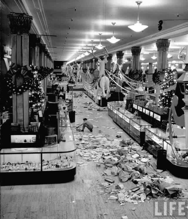 "Macy's employee cleaning up after the Christmas 1948 sale.  ""Black Friday"" is a product of Philadelphia, where the term was coined by local police to describe the overabundance of shoppers and general mobs the day after Thanksgiving, traditionally the start of the Holiday Season."