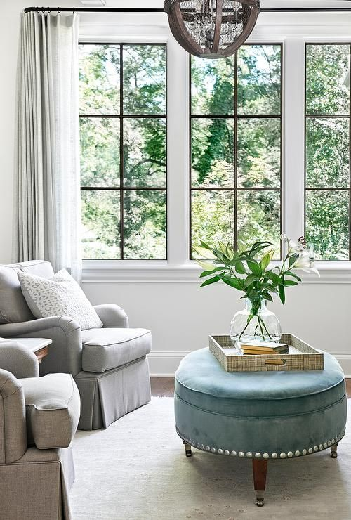 Windows covered with gray curtains illuminate a lovely transitional living room furnished with two gray roll arm chairs placed on a light gray rug angled towards a blue oval ottoman topped with a grasscloth tray placed beneath a wood and metal sphere pendant.
