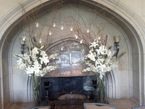 tall vases filled with curly willow, white orchids, white lilies and peacock feathers.  Hanging glass globes with LED lights inside. Designed By: hillside-consultants.com