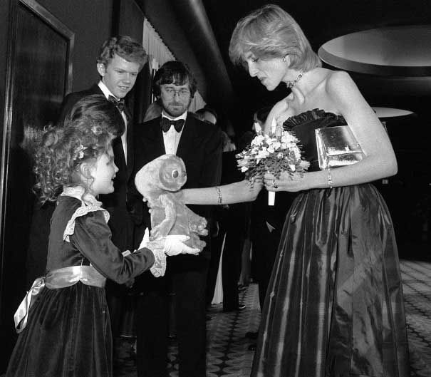 Drew Barrymore giving Princess Diana an E.T.-doll while Robert MacNaughton and Steven Spielberg is looking on at the London premiere of E.T.